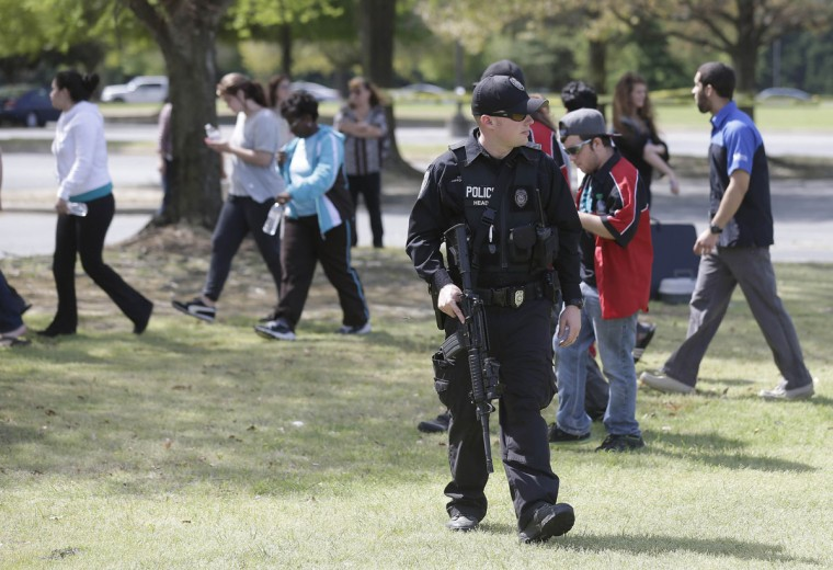 A police officer stands by as students and faculty are allowed to return following a lockdown at Wayne Community College, in Goldsboro, N.C., Monday, April 13, 2015. One person was killed in a shooting at the community college that was locked down as authorities searched for a gunman, officials said. (AP Photo/Gerry Broome)