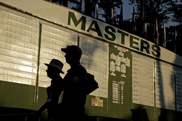 Spectators walk past the leader board before the first round of the Masters golf tournament Thursday, April 9, 2015, in Augusta, Ga. (AP Photo/Charlie Riedel)