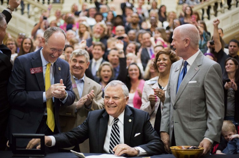 Georgia Gov. Nathan Deal, center, smiles after signing a medical marijuana bill into law as the bill sponsor, Rep. Allen Peake, R-Macon, left, looks on along with Sen. Butch Miller, R-Gainesville, right, during a ceremony at the Statehouse, Thursday, April 16, 2015, in Atlanta. The bill makes Georgia the 38th state to have one and legalizes possession of cannabis oil for treatment of certain medical conditions. (AP Photo/David Goldman)