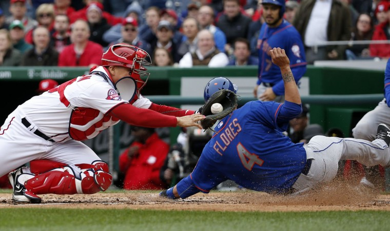New York Mets' Wilmer Flores (4) is safe at home as Washington Nationals catcher Jose Lobaton (59) can't make the tag in time during the sixth inning of a baseball game at Nationals Park, Thursday, April 9, 2015, in Washington. (AP Photo/Alex Brandon)