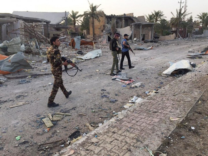 Iraqi security forces and tribal fighters walk down a street after regaining control of the northern neighborhoods, following overnight heavy clashes with Islamic State group militants, in Ramadi, 70 miles (115 kilometers) west of Baghdad, Iraq, Thursday, April 23, 2015. (AP Photo)