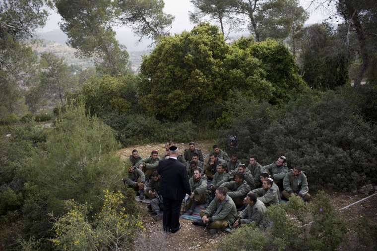 Moshe Eshkenazi, tells Israeli border police officers the story of his grandfather Moshe Pesach, rabbi of the Jewish community in Volos during World War II who saved more than one thousand Jews, during a ceremony marking the annual Holocaust remembrance day in the Martyr's forest near Moshav Kesalon, in central Israel, Thursday, April 16, 2015. Sirens sounded across Israel on Thursday morning, bringing life to a standstill as millions of Israelis observed a moment of silence to honor the memory of the 6 million Jews killed in the Nazi Holocaust during World War II. (AP Photo/Oded Balilty)