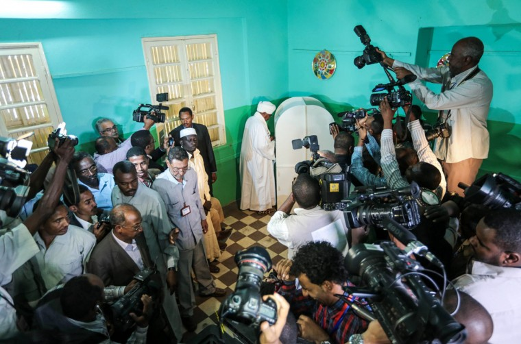 Journalists gather around President Omar al-Bashir as he votes on the first day of presidential and legislative elections, in Khartoum, Sudan, Monday, April 13, 2015. Sudan began voting Monday in an election expected to be won by al-Bashir, who has ruled Sudan unchallenged for 25 years. (AP Photo/Mosa'ab Elshamy)