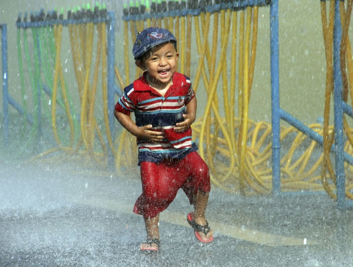 A boy runs as he is splashed with water during the opening ceremony of the annual Thingyan water festival celebrations outside Yangon City Hall in Yangon, Myanmar Monday, April 13, 2015. Myanmar began celebrating its annual days-long water festival, known as Thingyan, on Monday, marking the new year according to the traditional Burmese lunisolar calendar. (AP Photo/Khin Maung Win)