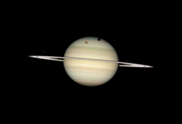 Image from the Hubble Space Telescope shows four moons of Saturn passing in front of their parent planet. (2009 NASA photo distributed by AP)