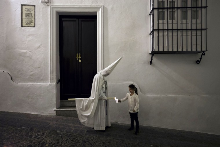 "A girl collects wax from a penitent large candle during the Holy Week procession of ""Nuestro Senor Atado a la Columna, Maria Santisima de la Paz y San Juan Evangelista"" in Arcos de la Frontera, Spain, Tuesday, March 31, 2015. Hundreds of processions take place throughout Spain during the Easter Holy Week. (AP Photo/Daniel Ochoa de Olza)"