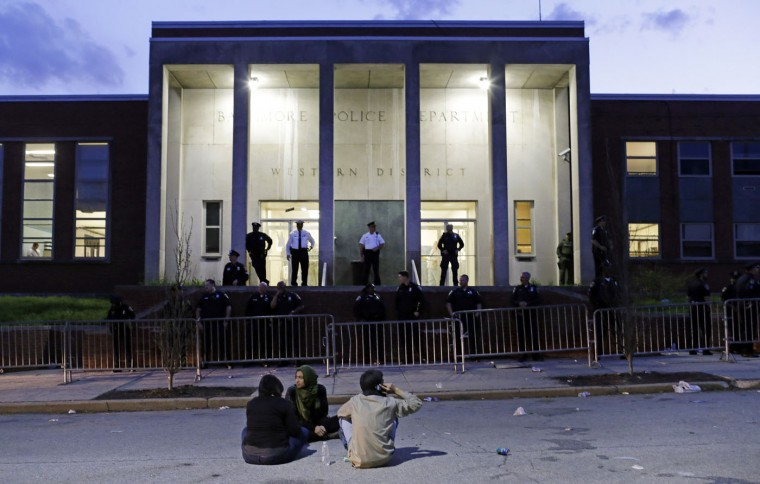 Protesters sit outside the Baltimore Police Department's Western District police station at the end of a march for Freddie Gray, Tuesday, April 21, 2015, in Baltimore. Gray died from spinal injuries a week after he was arrested and transported in a police van. (AP Photo/Patrick Semansky)