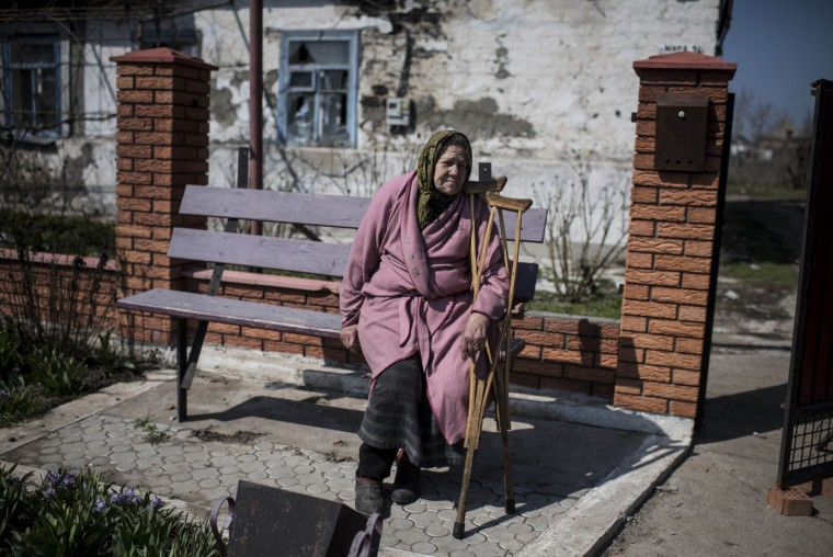 An elderly woman sits in front of her damaged house in the village of Shyrokyne, eastern Ukraine, Thursday, April 16, 2015. Shyrokyne, a village on the Azov Sea that has been the epicenter of recent fighting, has changed hands repeatedly throughout the conflict. (AP Photo/Evgeniy Maloletka)