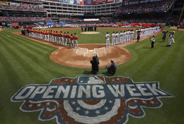 The Texas Rangers and the Houston Astros take the field for the national anthem before the Rangers' home opener on Friday, April 10, 2015. (AP Photo/Brad Loper)