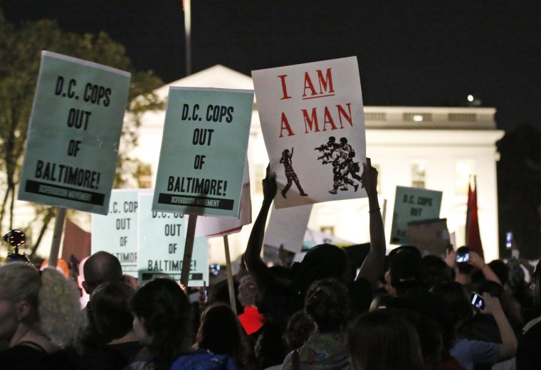 Protestors hold signs during a protest to support the rallies in Baltimore, in front of the White House, Wednesday, April 29, 2015 in Washington. Freddie Gray died from spinal injuries about a week after he was arrested and transported in a Baltimore police van. (AP Photo/Alex Brandon)