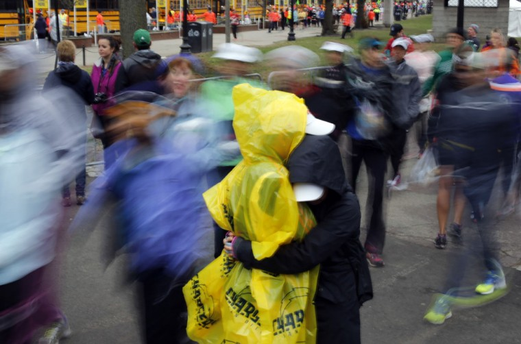 Boston Marathon runner Tenee Ramsdell, left, gets a hug from Evangline Gersish, both from San Diego, before boarding a shuttle bus in Boston to the starting line in Hopkinton, Mass., Monday, April 20, 2015. (AP Photo/Robert F. Bukaty)