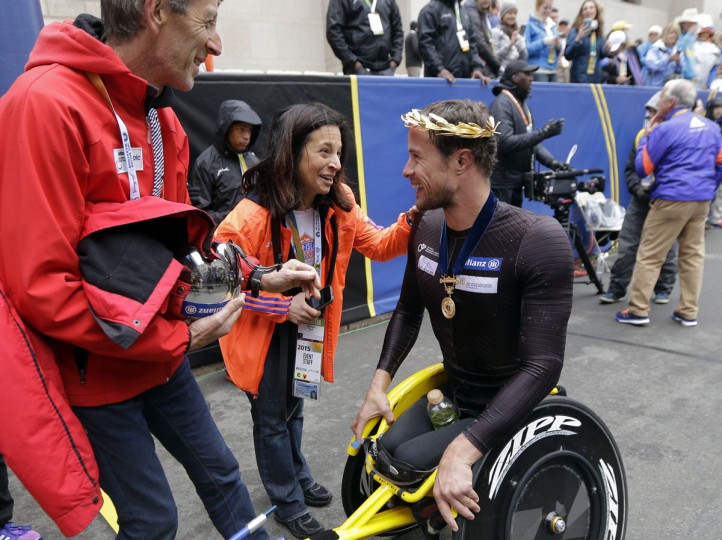 Marcel Hug, of Switzerland, is congratulated after winning the wheelchair division of the Boston Marathon Monday, April 20, 2015 in Boston. (AP Photo/Elise Amendola)