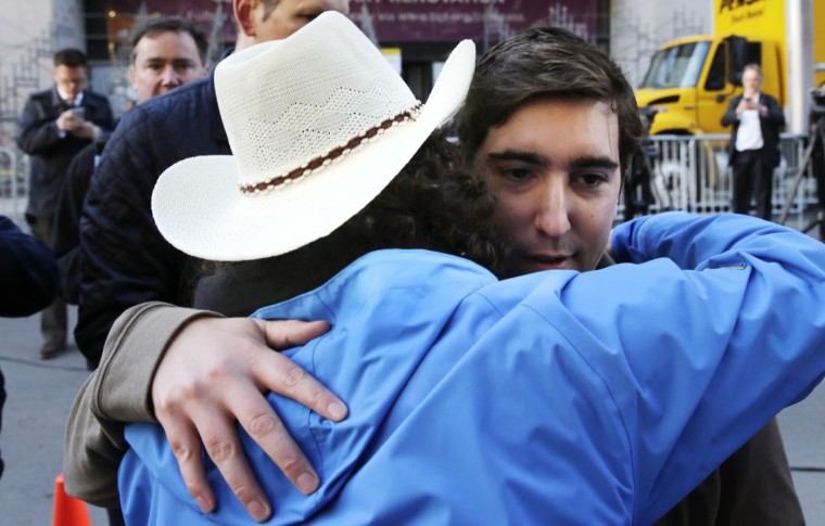 Boston Marathon survivor Jeff Bauman, right, is embraced by Carlos Arredondo, who helped save his life, near the finish line of the Boston Marathon in Boston, Wednesday, April 15, 2015. Boston marked the second anniversary of the 2013 marathon bombings with a subdued remembrance that includes a moment of silence, the pealing of church bells and a call for kindness. (AP Photo/Charles Krupa)