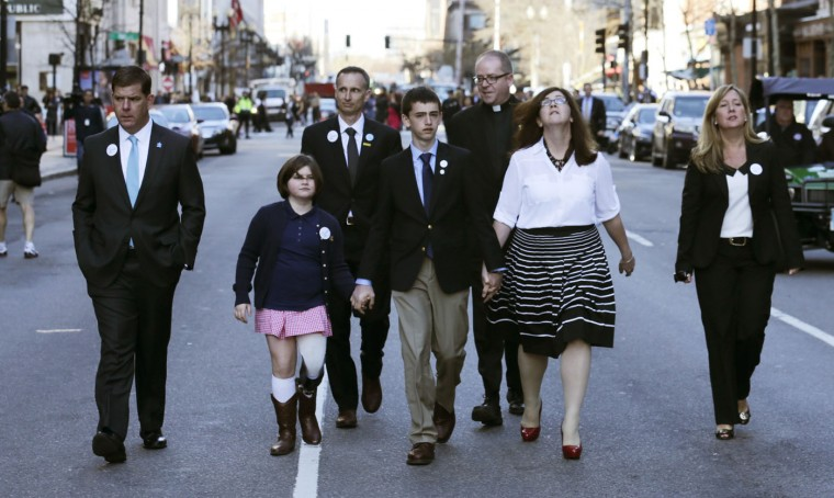 Boston Marathon survivor Jane Richard holds the hand of her brother Henry, center, as their family walks down Boylston Street with Boston Mayor Marty Walsh, left, after a ceremony honoring victims and survivors at one of two blast sites near the finish line of the Boston Marathon in Boston, Wednesday, April 15, 2015. Boston marked the second anniversary of the 2013 marathon bombings with a subdued remembrance that includes a moment of silence, the pealing of church bells and a call for kindness. (AP Photo/Charles Krupa)