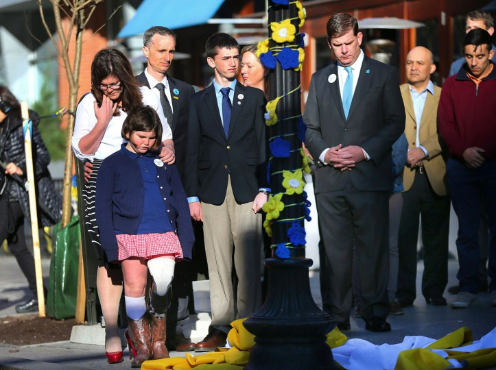 Boston Mayor Marty Walsh, right. looks down after Boston Marathon survivor Jane Richard, left, and her brother Henry removed a drape covering a memorial honoring victims and survivors at one of two blast sites near the finish line of the Boston Marathon in Boston, Wednesday, April 15, 2015. Parents, Bill and Denise Richards, back, stood by during the unveiling. Boston marked the second anniversary of the 2013 marathon bombings with a subdued remembrance that includes a moment of silence, the pealing of church bells and a call for kindness. The children lost their brother Martin Richard while standing with him during one of the explosions. (John Tlumacki/The Boston Globe via AP)