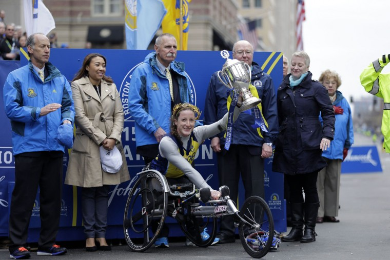 Tatyana McFadden, of Russia, hoists her trophy after winning the women's wheelchair division of the Boston Marathon Monday, April 20, 2015 in Boston. (AP Photo/Elise Amendola)