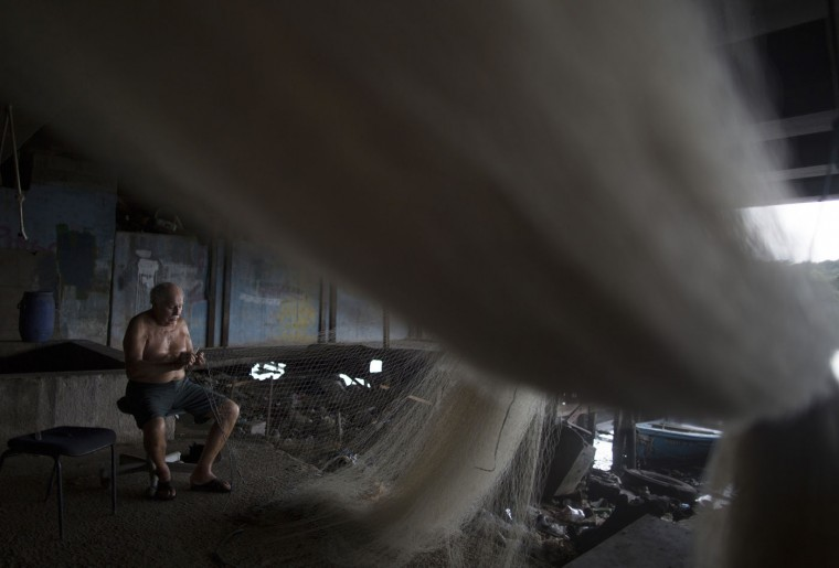 "In this Feb. 28, 2015 photo, Manuel Batista de Moraes repairs a fishing net as he sits at the dock, located on a canal that connects to Guanabara bay, in the Vila Pinheiro slum, part of the Mare complex in Rio de Janeiro, Brazil. ""In the past we fished all kinds of species right here in this canal,"" said the 76-year-old fisherman who now repairs nets instead of going out into the water. ""Now it's just full of filth and more filth."" (AP Photo/Leo Correa)"