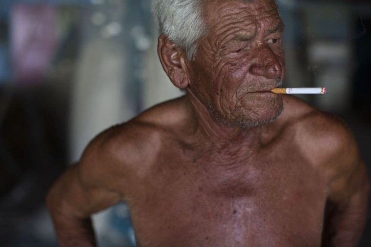 In this March 3, 2015 photo, fisherman Cicero Romao Batista smokes after a morning of fishing in Guanabara Bay at the dock in the Vila Pinheiro slum, part of the Mare complex in Rio de Janeiro. The 69-year-old widower who's been fishing since the 1970s said he still fishes to supplement his monthly government pension. (AP Photo/Leo Correa)