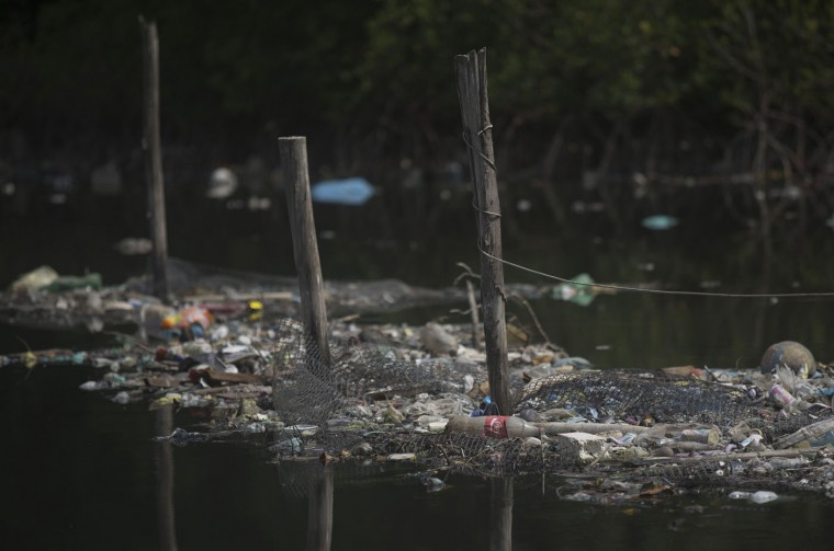 In this Feb. 28, 2015 photo, trash floats on the water along a fence line in Guanabara bay in Rio de Janeiro, Brazil. About 30 fishermen work out of the garbage-strewn docks sitting right under the Red Line highway leading to the international airport, where the polluted waters of the Fundao and Cunha canals meet to flow into the bay. (AP Photo/Leo Correa)