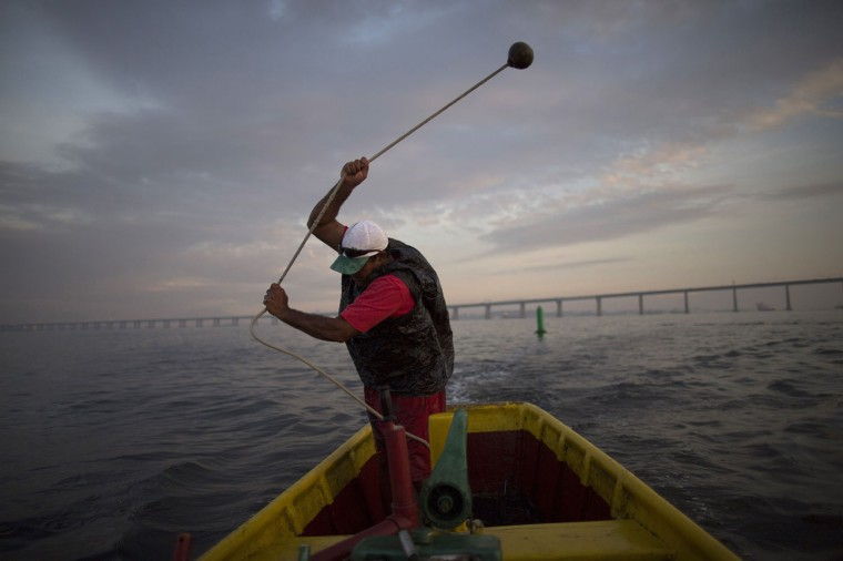 In this Feb. 28, 2015 photo, fisherman Edmo Rodrigues da Costa hurls a weight into the water as he casts a net in Guanabara bay in Rio de Janeiro, Brazil. For 30 years, the 59-year-old fisherman has trolled the bay that will host Olympic sailing events in 2016, setting his nets at dawn, hoping to catch sea bass, Atlantic bigeyes and shrimp. (AP Photo/Leo Correa)