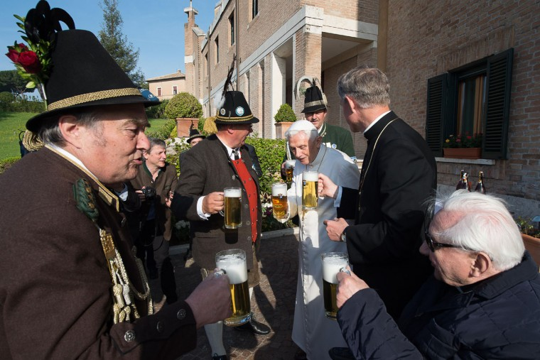 Pope Emeritus Benedict XVI, third from right, toasts for his 88th birthday with his brother Georg Ratzinger, right, Monsignor Georg Gaenswein, second from right, and members of a group from his hometown Bavaria region, in the Vatican gardens, Thursday, April 16, 2015. (L'Osservatore Romano/Pool Photo via AP)