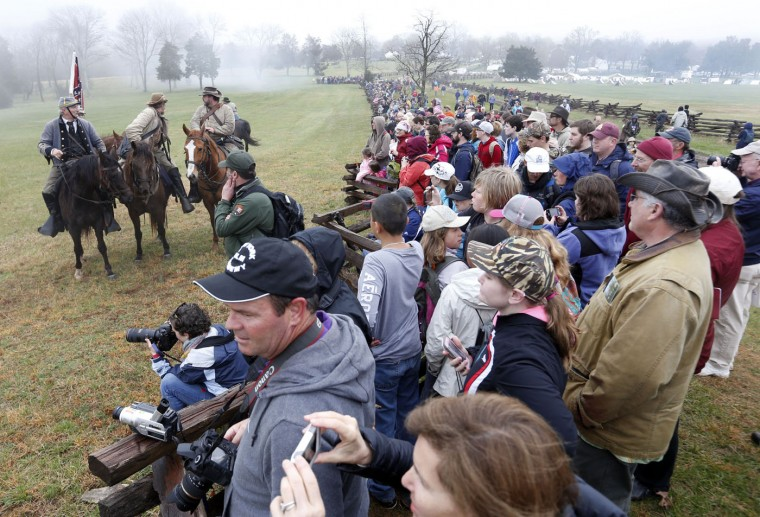 Confederate officers watch the battle along with visitors during a re-enactment of the Battle of Appomattox Courthouse as part of the commemoration of the 150th anniversary of the surrender of the army of Northern Virginia at Appomattox Court House in Appomattox, Va., Thursday, April 9, 2015. The battle was the final battle of the army of Confederate General Robert E. Lee before his surrender to Union troops. (AP Photo/Steve Helber)