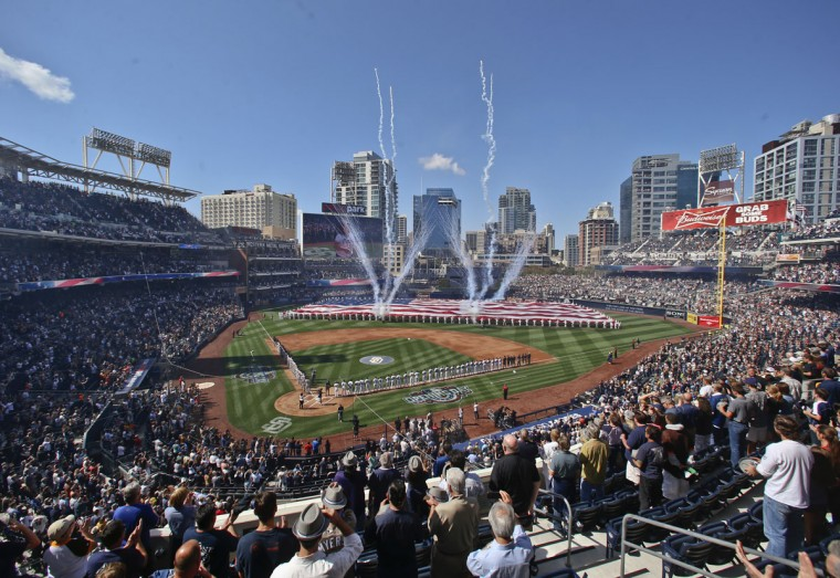 Players line the base lines at Petco Park as a large flag is displayed during the San Diego Padres' home opener against the San Francisco Giants on Thursday, April 9, 2015, in San Diego. (AP Photo/Lenny Ignelzi)