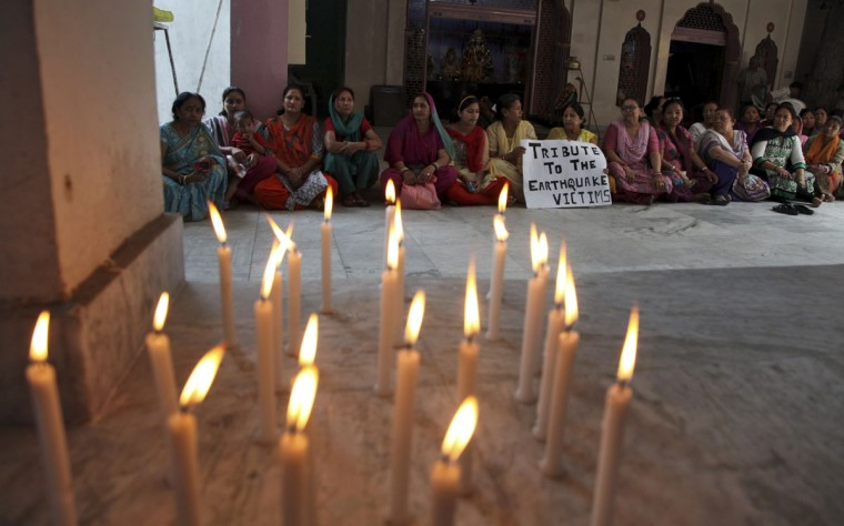 Indian women offer prayers for victims of Nepal's earthquake, at a temple in Gorkha Nagar in Jammu, India, Monday, April 27, 2015. A strong magnitude earthquake shook Nepal's capital and the densely populated Kathmandu valley on Saturday devastating the region and leaving tens of thousands shell-shocked and sleeping in streets. (AP Photo/Channi Anand)