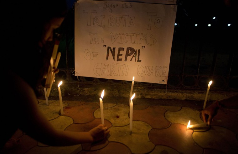 Indian students light candles on a pavement as tribute to victims of Nepal's earthquake, in Gauhati, India, Sunday, April 26, 2015. Saturday's earthquake centered outside Kathmandu, the capital of Nepal, was the worst to hit the South Asian nation in over 80 years. It destroyed swaths of the oldest neighborhoods of Kathmandu, and was strong enough to be felt all across parts of India, Bangladesh, China's region of Tibet and Pakistan. (AP Photo/ Anupam Nath)