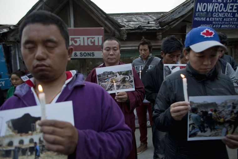 Exile Tibetans hold photographs showing devastation in Nepal during a candlelit vigil in solidarity with the people affected by the earthquake in Nepal and the border areas of India and China, in Dharmsala, India, Sunday, April 26, 2015. Saturday's earthquake centered outside Kathmandu, the capital of Nepal, was the worst to hit the South Asian nation in over 80 years. It destroyed swaths of the oldest neighborhoods of Kathmandu, and was strong enough to be felt all across parts of India, Bangladesh, China's region of Tibet and Pakistan. (AP Photo/Ashwini Bhatia)