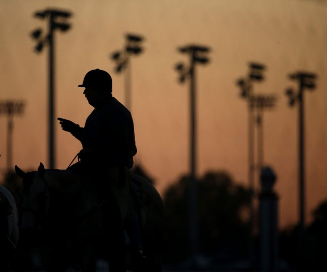 Trainer D. Wayne Lukas watches early morning workouts at Churchill Downs in advance of Saturday's Kentucky Derby Monday, April 27, 2015, in Louisville, Ky. (AP Photo/Charlie Riedel)