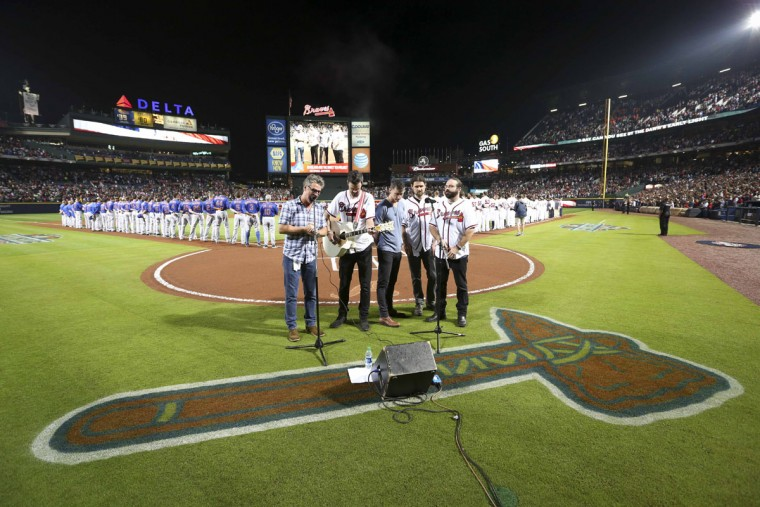 Ed Roland (left) and the Sweet Tea Project sing the National Anthem prior to the Atlanta Braves' home opener against the New York Mets, Friday, April 10, 2015, in Atlanta. The Braves won 5-3. (AP Photo/Kevin Liles)