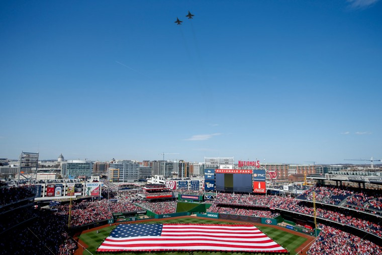 Jets perform a flyover as a large American flag is unfurled on the field before the Washington Nationals' home opener vs. the New York Mets at Nationals Park, Monday, April 6, 2015, in Washington. (AP Photo/Andrew Harnik)