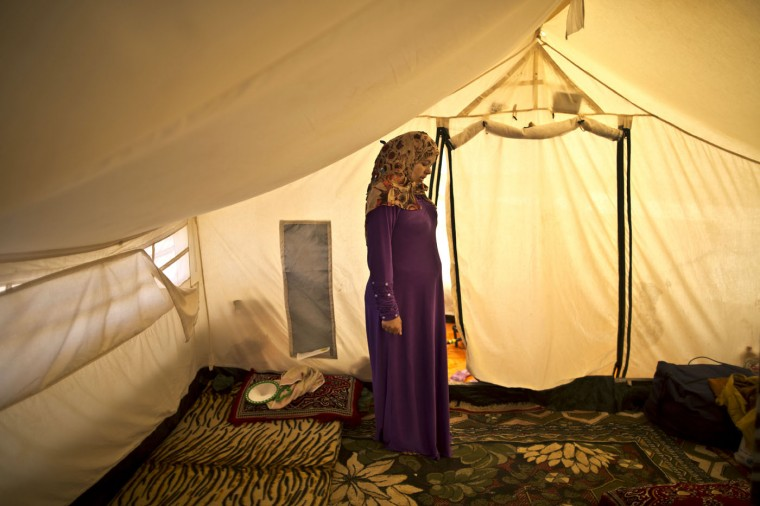 In this Tuesday, March 17, 2015 photo, Syrian refugee Adala Ismail, 32, who is six months pregnant, poses for a portrait inside her tent at an informal settlement near the Syrian border, on the outskirts of Mafraq, Jordan. Expectant mothers in these settlements often can't afford doctor visits and face potential health hazards because of lack of running water and other challenges. By contrast, pregnant women in Jordanís three recognized refugee camps have access to free services, including pre-natal care and delivery, according to the U.N. refugee agency. (AP Photo/Muhammed Muheisen)