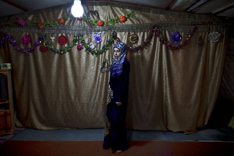 "In this Tuesday, March 17, 2015 photo, pregnant Syrian refugee Huda Alsayil, 20, poses for a portrait inside her tent at an informal tented settlement near the Syrian border, on the outskirts of Mafraq, Jordan. ""A couple of weeks ago, I couldnít feel my baby moving in my belly so I panicked and didnít know what to do since I can't afford heading to a clinic and check,"" says Alsayil, who fled fighting in Hama three years ago and is five months pregnant. (AP Photo/Muhammed Muheisen)"