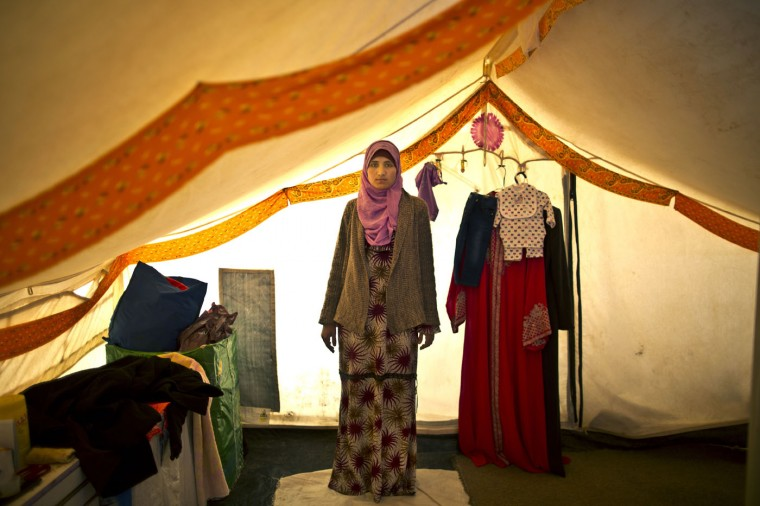 "In this Monday, March 16, 2015 photo, Syrian refugee Khalida Alfarraj, 22, who is pregnant with her first child, poses for a portrait inside her tent at an informal tented settlement near the Syrian border, on the outskirts of Mafraq, Jordan. She suffers from low blood sugar and dizziness two months into her pregnancy, but cannot afford medicine. ìI want to send a message to every pregnant woman in the world, feel blessed to have a safe roof and a family around you,"" she said. (AP Photo/Muhammed Muheisen)"