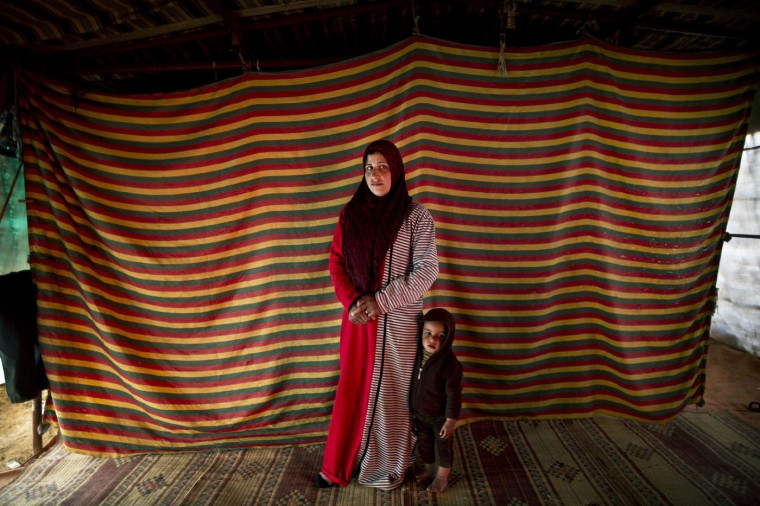 In this Monday, March 16, 2015 photo, Syrian refugee Shams Alhamadah, 24, who is two months pregnant with her fifth child, poses for a portrait with her son Ismail inside their tent at an informal tented settlement near the Syrian border, on the outskirts of Mafraq, Jordan. (AP Photo/Muhammed Muheisen)