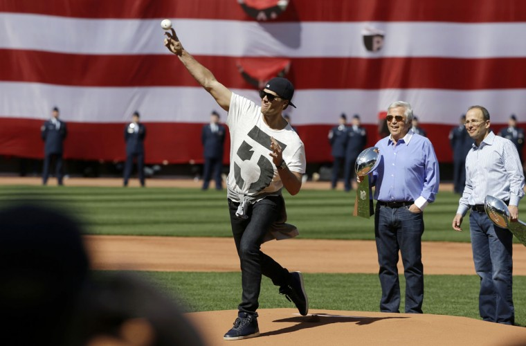 New England Patriots quarterback Tom Brady, center, throws a ceremonial first pitch as Patriots owner Robert Kraft, second from right, and Patriots President Jonathan Kraft, right, each hold a Super Bowl trophy before a baseball game between the Boston Red Sox and the Washington Nationals, Monday, April 13, 2015, in Boston. (AP Photo/Steven Senne)