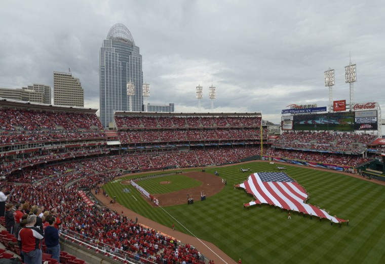 Pittsburgh Pirates and Cincinnati Reds players line the baseline during the singing of the National anthem before the Reds' home opener on Monday, April 6, 2015 in Cincinnati. (AP Photo/Michael E. Keating)