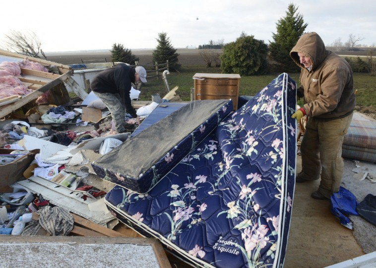 Jerry Richardson, right, of Hinckley, Ill., right helps search for personal belongings at the Hernandez home in Rochelle, Ill. Friday morning, April 10, 2015, after at least two tornadoes churned through six north-central Illinois counties. Richardson is a relative of the family. (AP Photo/Daily Herald, Paul Michna)