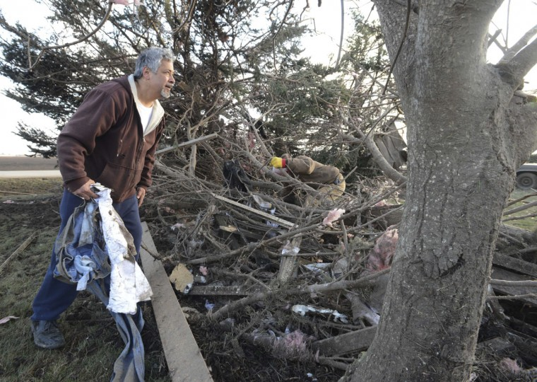 Eloy Hernandez, of Rochelle, Ill. looks for his belongings in the remains of his home early Friday morning April 10, 2015, after the home was destroyed by a tornado Thursday night. The National Weather Service says at least two tornadoes churned through six north-central Illinois counties Thursday night. One person was killed in the small town of Fairdale, Ill. (AP Photo/Daily Herald, Paul Michna)