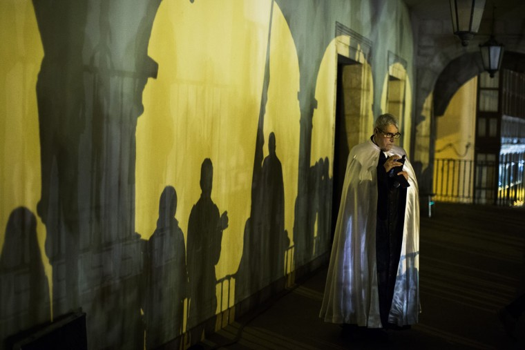 "A penitent from ""Jesus en su Tercera Caida"" brotherhood takes pictures as he watches the procession in Zamora, Spain, Monday, March 30, 2015. Hundreds of processions take place throughout Spain during the Easter Holy Week. (AP Photo/Andres Kudacki)"