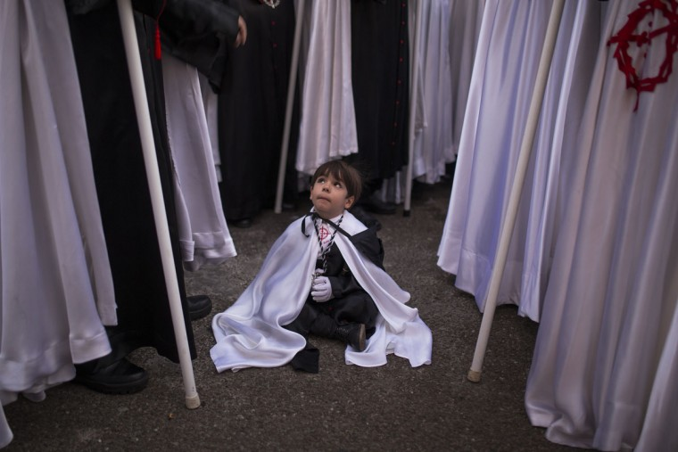 "A child looks at other penitents from ""Jesus en su Tercera Caida"" brotherhood as they wait to start a procession in Zamora, Spain, Monday, March 30, 2015. Hundreds of processions take place throughout Spain during the Easter Holy Week. (AP Photo/Andres Kudacki)"