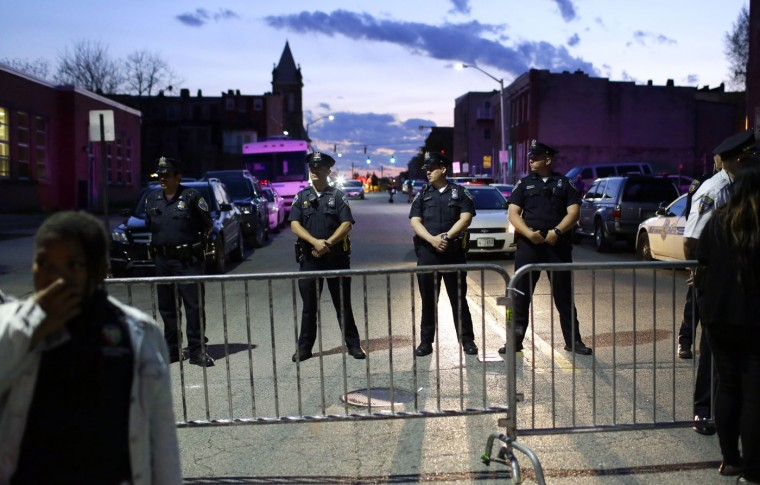 Members of the Baltimore Police Department stand behind barriers outside of the Western District police station during a march for Freddie Gray, Tuesday, April 21, 2015, in Baltimore. Gray died from spinal injuries a week after he was arrested and transported in a police van. (AP Photo/Patrick Semansky)