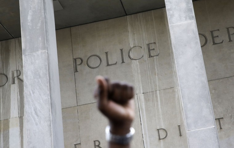 A protestor raises his fist outside of the Baltimore Police Department's Western District police station during a march and vigil for Freddie Gray, Tuesday, April 21, 2015, in Baltimore. Gray died from spinal injuries a week after he was arrested and transported in a police van. (AP Photo/Patrick Semansky)
