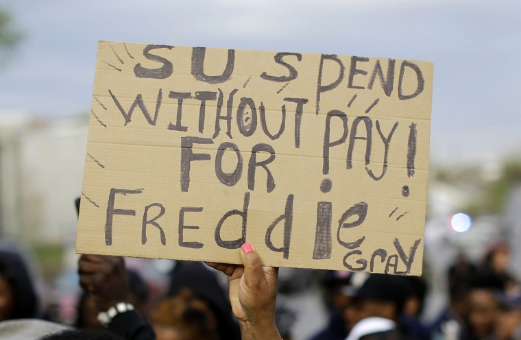 A woman holds a sign during a protest for Freddie Gray outside the Baltimore Police Department's Western District police station, Wednesday, April 22, 2015, in Baltimore. Gray died from spinal injuries a week after he was arrested and transported in a police van. (AP Photo/Patrick Semansky)