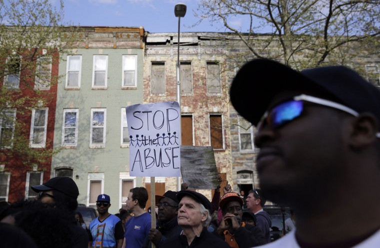 Protestors march outside of the Baltimore Police Department's Western District police station during a march and vigil for Freddie Gray, Tuesday, April 21, 2015, in Baltimore. Gray died from spinal injuries a week after he was arrested and transported in a police van. (AP Photo/Patrick Semansky)