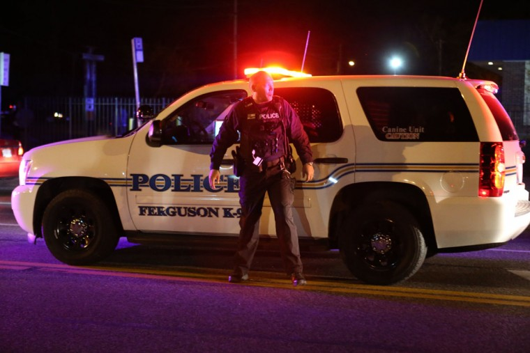 A Ferguson police officer stands on West Florissant Avenue as protesters block traffic in Ferguson, Mo., Tuesday night, April 28, 2015. Looting, fires and gunfire broke out overnight in Ferguson during protests in response to the death of Freddie Gray in police custody in Baltimore. (David Carson/St. Louis Post-Dispatch via AP)