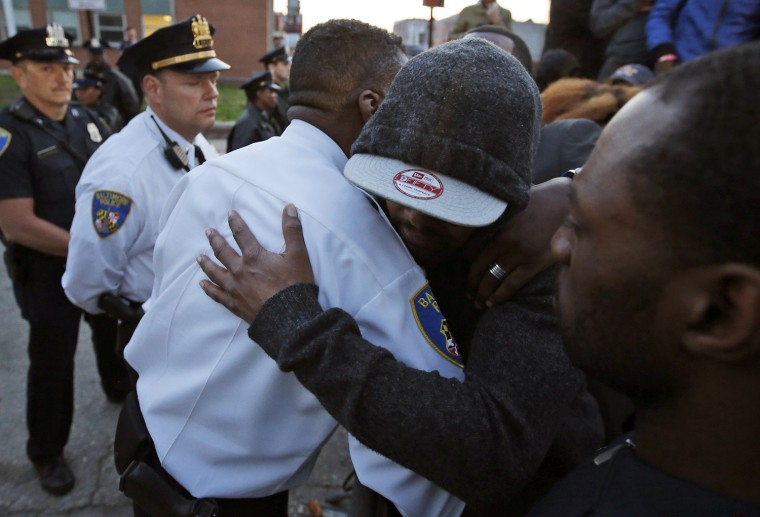 A marcher embraces Baltimore Police Lt. Col. Melvin T. Russell, in front of the department's Western District police station during a march for Freddie Gray, Wednesday, April 22, 2015, in Baltimore. Gray died from spinal injuries about a week after he was arrested and transported in a police van. (AP Photo/Alex Brandon)