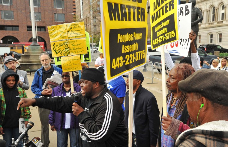"The Rev. Cortly ""C.D."" Witherspoon, front left, president of the Baltimore City chapter of the Southern Christian Leadership Conference, speaks at a protest outside City Hall about Freddie Gray in Baltimore, Monday, April 20, 2015. Baltimore's top police officials, mayor and prosecutor sought to calm a ""community on edge"" Monday while investigating how Gray suffered a fatal spine injury while under arrest. Six officers have been suspended, but investigators say they still don't know how it happened. (Amy Davis/The Baltimore Sun via AP)"